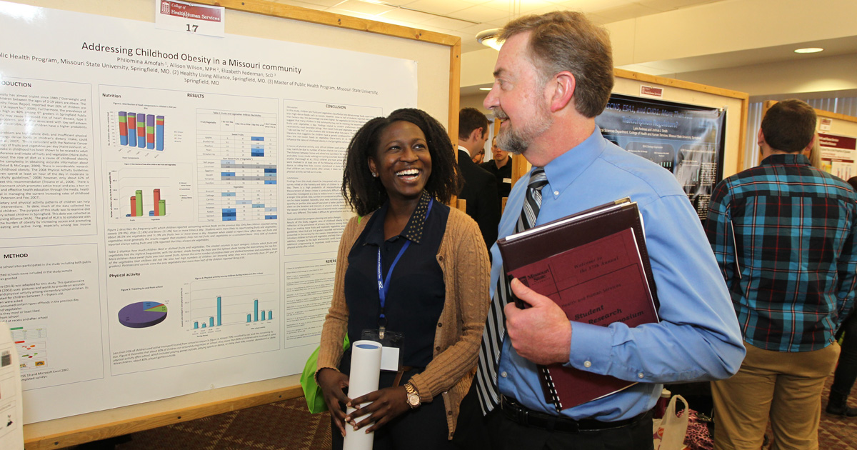 Student and professor discussing her research at the Graduate Interdisciplinary Forum