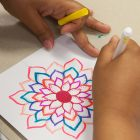 Young person drawing with markers