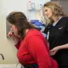 Occupational therapist helping a patient brush teeth