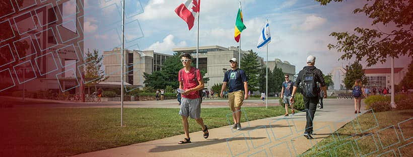 Students walking by colorful international flags for Facebook
