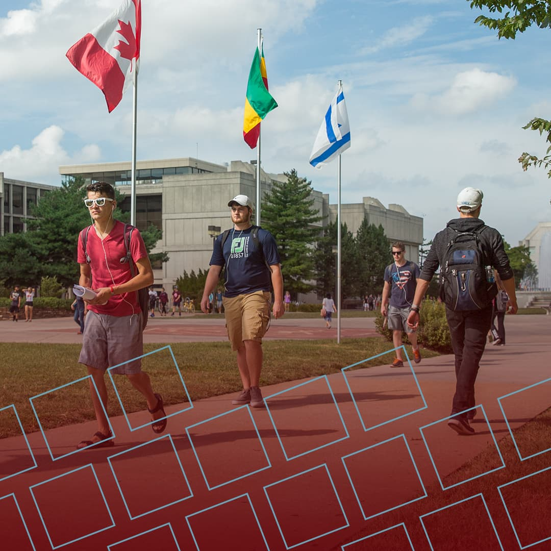 Students walking by colorful international flags for Instagram