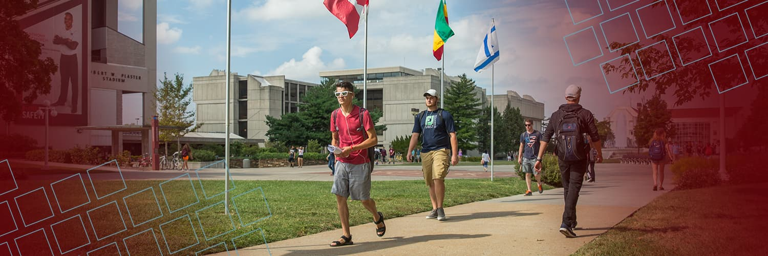 Students walking by colorful international flags for Twitter