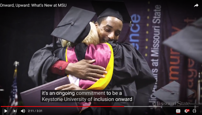 student hugging professor at graduation