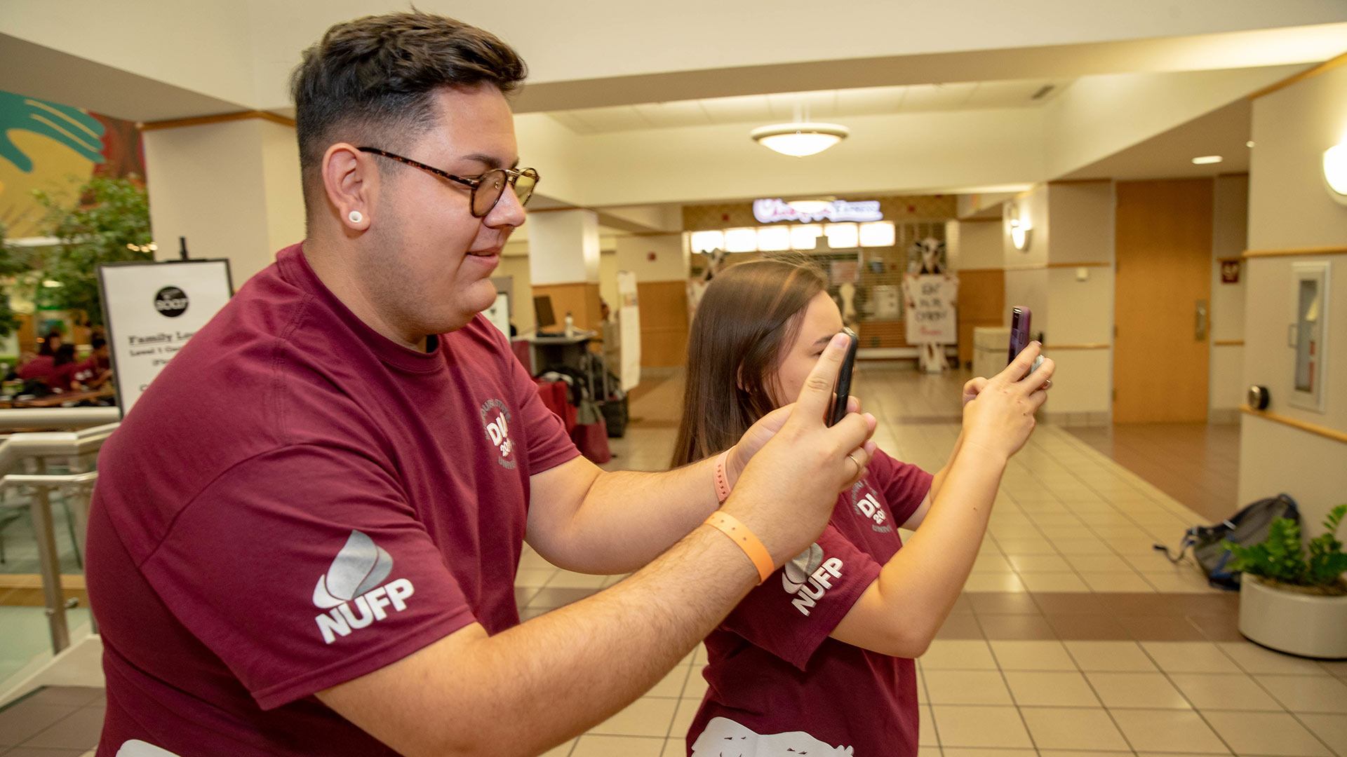 Missouri State students in maroon T-shirts taking photos with their smartphones.